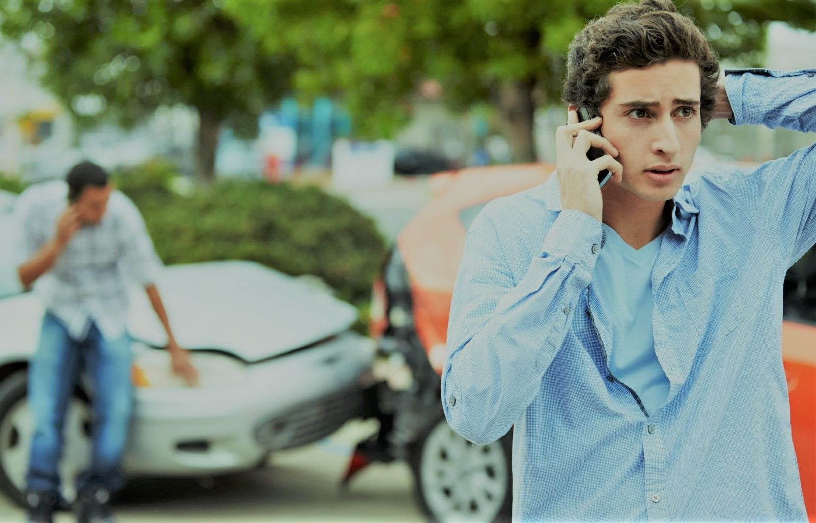 young man on cell phone at the scene of a car accident